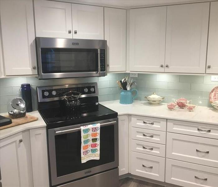 Kitchen with white cabinets, teal backsplash, and black oven