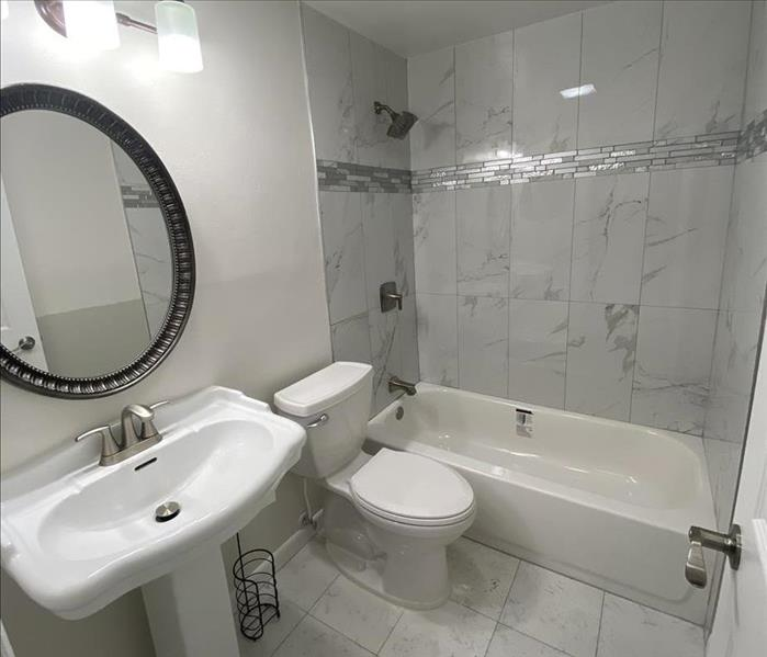 White bathroom with toilet, sink and bathtub