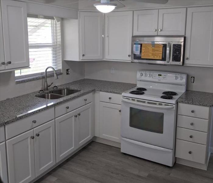Kitchen with white cabinets and appliances and grey flooring