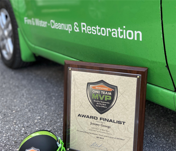 award sitting in front of a green truck on the road
